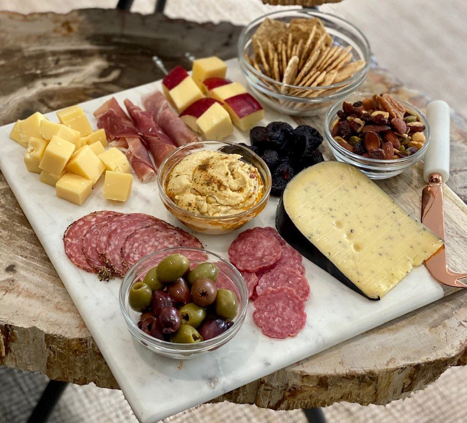 A charcuterie board looks terrific on a white background.